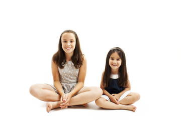 Older and younger sisters sitting on the floor. Isolated on white background
