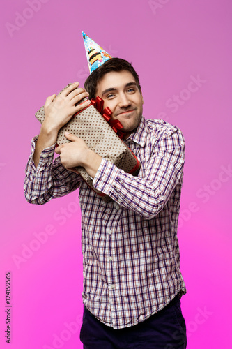 Happy Young Man Embracing Birthday Gift In Box Over Purple Background