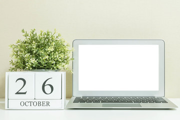 White wooden calendar with black 26 october word with white blank space at center of computer notebook on white wood desk and cream wallpaper textured background , selective focus at the calendar