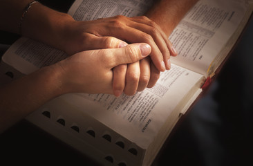 Holding Hands And Praying Over The Bible