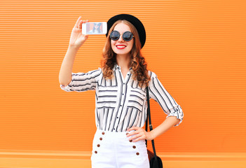 Fashion young woman model taking picture self portrait on smartp