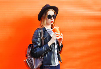Fashion pretty young woman drinking fresh fruit juice from a cup