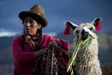 Woman in traditional clothing with llama in Cuzco, Peru