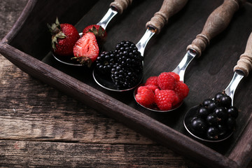 mixed strawberries, raspberries, blueberries and blackberries on vintage metal spoons