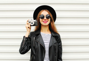Fashion look, pretty young woman model with retro film camera we