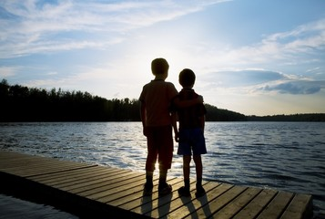Silhouette Of Children On A Dock