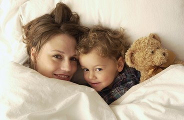 Mother And Son Laying In Bed