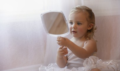 Little Girl Looking At Herself In A Hand Mirror