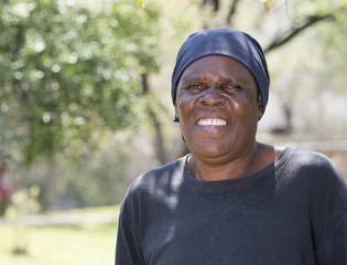 Smiling Older South African Woman Standing in Yard Where she is Gardener