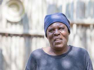 Smiling Older South African Woman Standing in Front of Shed