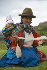 Cuzco, Peru; Woman Spinning Alpaca Wool While Carrying Her Baby On Her Back