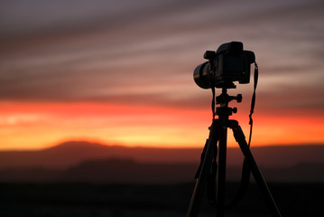 Camera set on a tripod aimed at a silhouette of a landscape during sunset