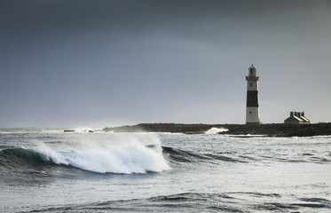 Lighthouse on Inis Oirr, with waves breaking on the rugged western coastline of Ireland; Inis Oirr, Aran Islands, Ireland