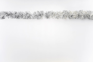 One Silver Strand Of Tinsel Garland On White Background Studio Portrait