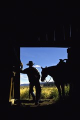 Silhouette Of A Cowboy Holding His Horse's Reins And Looks Out Of The Barn As He Contemplates The Day; Seneca, Oregon, United States Of America