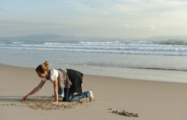 A Girl Drawing In The Sand At Los Lances Beach Along Costa De La Luz; Tarifa, Cadiz, Andalusia, Spain