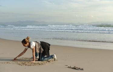 A Girl Drawing In The Sand At Los Lances Beach Along Costa De La Luz; Tarifa, Cadiz, Andalusia, Spain