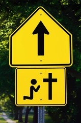 Willmar, Minnesota, United States Of America; A Sign With An Arrow And A Person Kneeling At A Cross