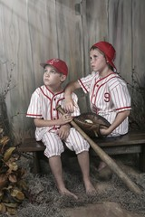 Two Boys Wearing Baseball Uniforms Sitting On A Bench