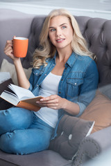 Young blond woman sitting on couch with book and cup