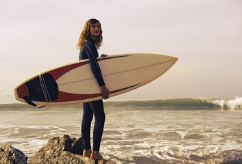 Young Woman With Her Surfboard At The Beach; Tarifa, Cadiz, Andalusia, Spain