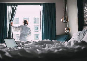 Woman in white robe stay hear the window in hotel room