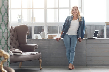 Pretty blond lady standing at big panoramic window