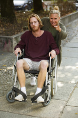 man in wheelchair and woman showing him something