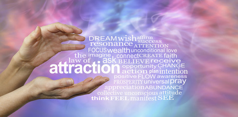 The Law of Attraction Word Cloud - female hands with the word ATTRACTION floating between surrounded by a relevant word cloud on a pink and blue misty wispy energy formation background