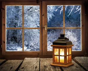 Weihnachten - Laterne vor dem Fenster einer Holzhütte in verschneitem Winterwald