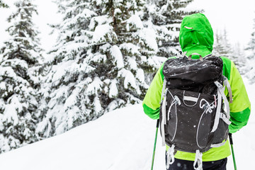 Winter hike in white woods. Man walking with backpack on snowy trail.