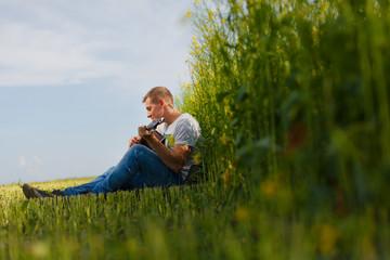 gay single man plays guitar in a field.