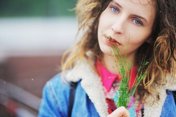 Young charming girl with dreads with a bouquet of wild herbs in