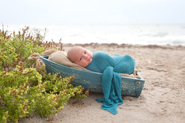 Newborn Baby Boy Sleeping in a Tiny Boat