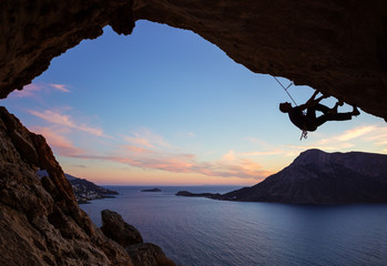 Male climber climbing along roof in cave at sunset