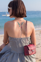 Fashionable young woman with tattoo on her back in black and white clothes with a luxury snakeskin handbag on the beautiful beach of tropicsl island Bali, Indonesia. Nusa Dua area. Amazing ocean view.