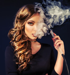 Young, beautiful girl in club dress and perfect make up smoke a