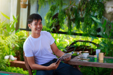 smiling asian casual man reading magazine