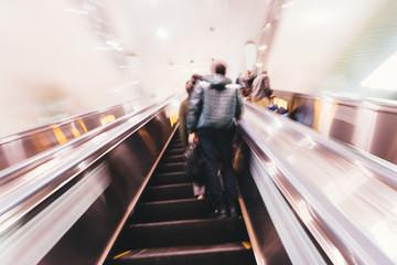 Moton blured commuters on escalator.