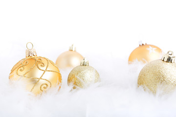 Christmas baubles on a feathery surface, brightly lit