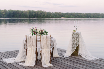 Decoration for romantic dinner on the riverside. Decorated table with flower composition and food on it and two chairs with lace