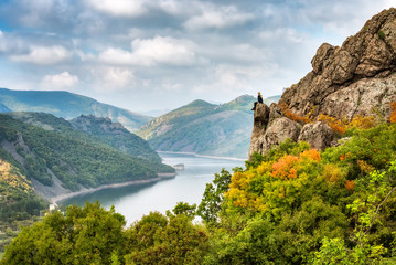 Autumn from the top / A woman on the top of a rock enjoys the view of an autumn forest and Studen Kladenec dam, Bulgaria
