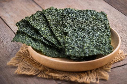 Crispy dried seaweed on wooden plate