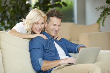 Happy couple with laptop at home. Close-up of a middle aged couple sitting on sofa in living room and using laptop.