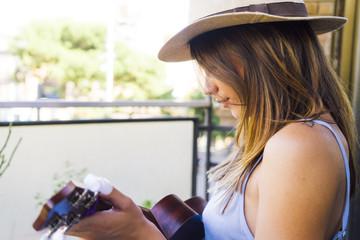 Smiling girl in hat playing music using ukulele