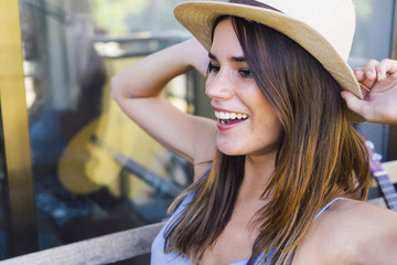 Cheerful girl laughing in white hat with brown ribbon