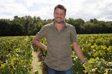 Happy and smiling winemaker man in a his vineyard