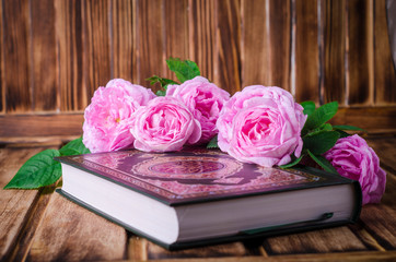 Roses and Quran on wooden background. Selective focus on roses