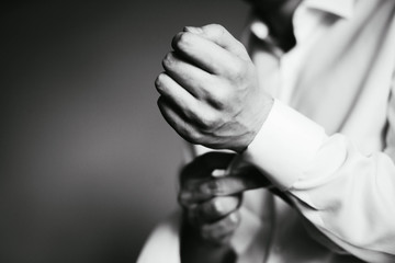 groom fasten his cuffs on the sleeve