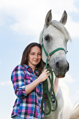 Beautiful young woman with her lovely white horse